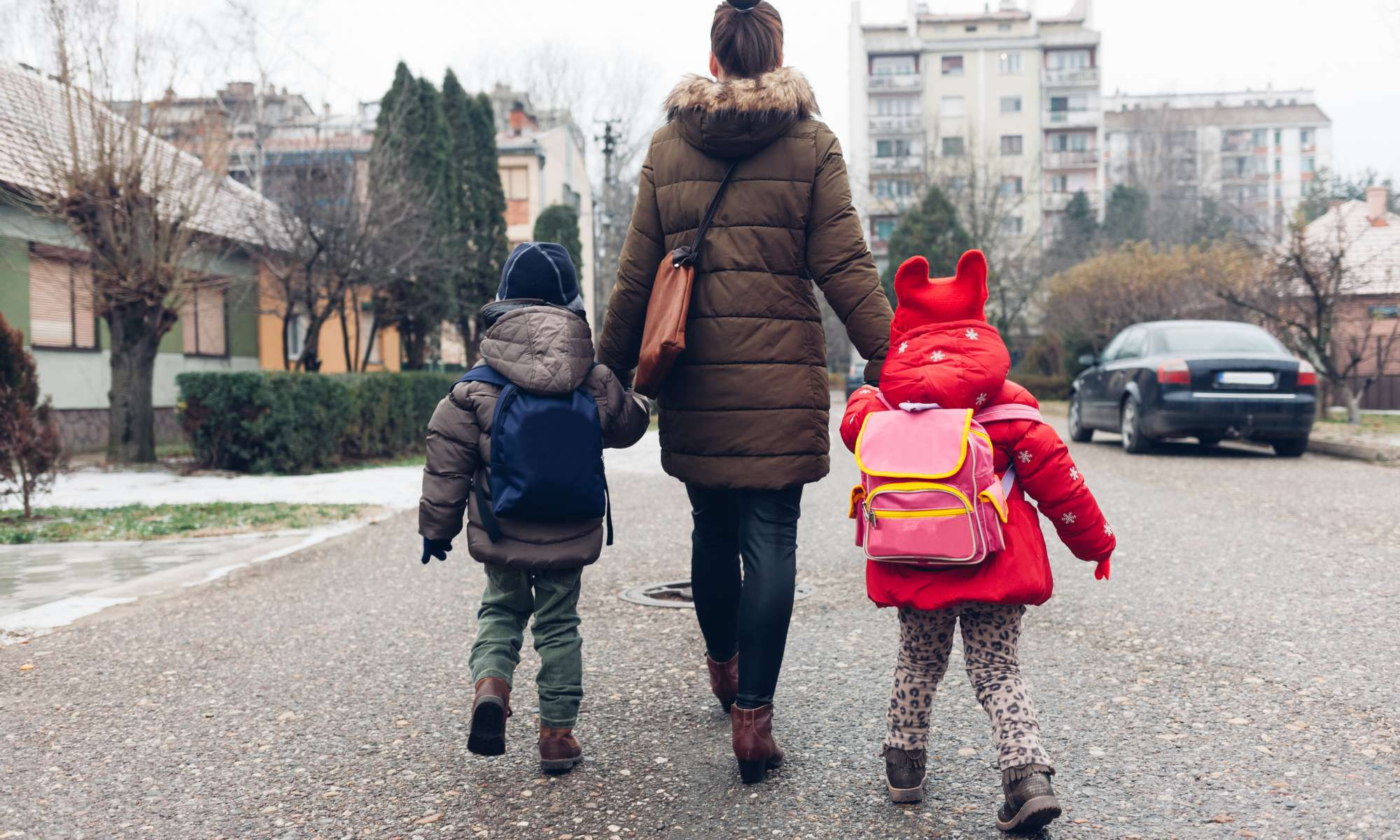 A Back-to-School Guide for Talking to your kids about consent — sara nasserzadeh — photo shows a parent holding two children's hands; they are wearing backpacks.