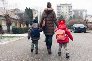 A Back-to-School Guide for Talking to your kids about consent —sara nasserzadeh — photo shows a parent holding two children's hands; they are wearing backpacks.